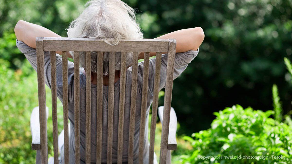 grauhaarige Frau im Garten